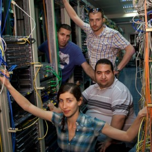 "Palestinian engineers Achmed Badir (top right) and Jafar Hajear (bottom right) of Ramallah-based Exalt Technologies meet with their Israeli teammates at Cisco near Tel Aviv, Oz Ben-Rephael (top left) and Michal Cohen (bottom left). Exalt provides R&D outsourcing to Cisco. Says Ben-Rephael: ""I think it is amazing that we can overcome the distance. We just needed that common target."" Adds Badir: ""There was a lot of curiosity by both sides."" (Photo: Heidi Levine)"